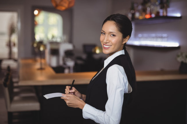 Smiling waitress writing order on notepad