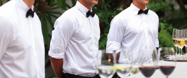 Waiters serving wine at a luxurious gathering
